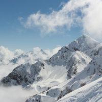 Unbefahrener Hang mit tiefhängenden Wolken im Hintergrund